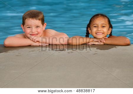 Portrait of Caucasian boy and mixed race girl in pool after swimming and playing together