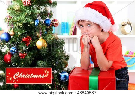 Child in Santa hat near Christmas tree with big gift