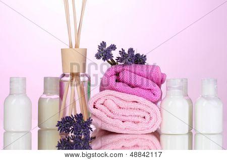 Bottle of air freshener, lavander and towels on pink background