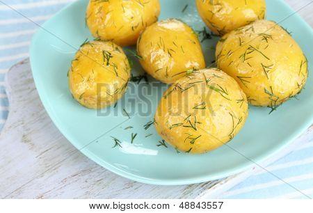 Boiled potatoes on platen on wooden board on napkin
