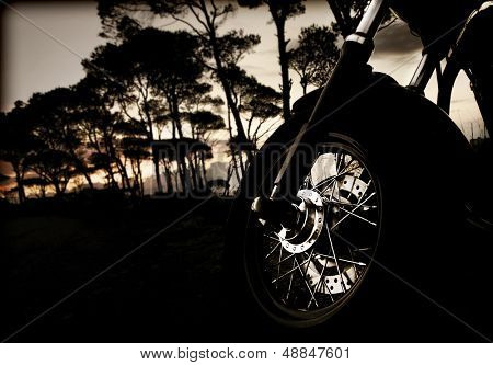 Closeup photo of motorcycle wheel on sunset, active lifestyle, extreme sport, dangerous transport in the forest at night, journey and freedom concept