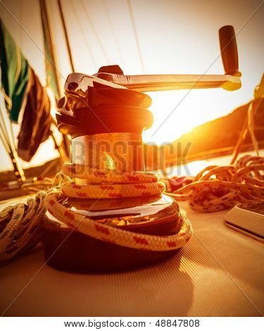 Closeup on crank handle of yacht in warm yellow sunset light, sailboat detail, active lifestyle, water sport, luxury transport, summer tourism concept