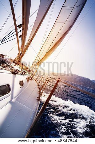 Yate de lujo en acción en el mar sobre fondo de atardecer, vela deportiva, transporte de agua, verano cruis