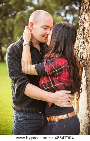 Romantic young couple portrait kissing tenderly standing next to a tree in a park
