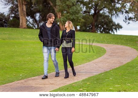 Smiling young couple holding hands walking in a park's path