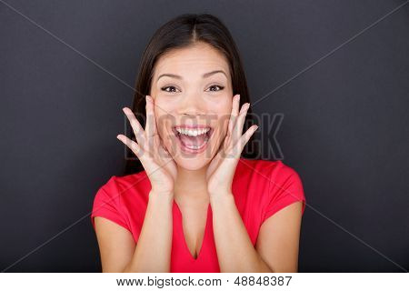 Screaming girl on black background yelling excited, happy and loud looking at camera. Young casual woman wearing red t-shirt. Multi-ethnic mixed race Asian Caucasian female girl model in studio.