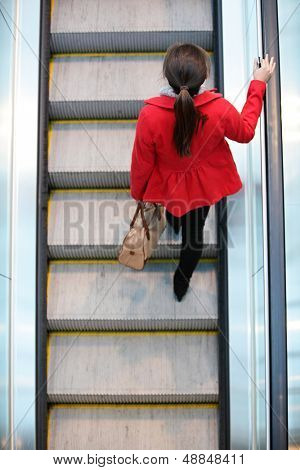 Urban people - woman commuter walking on escalator stairs in city. High angle view perspective from above showing young female professional commuting to work.