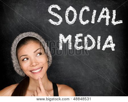 Social media concept with university student looking thinking at SOCIAL MEDIA text on blackboard. Female college student girl in front of black chalkboard. Trendy cool multiracial asian caucasian girl