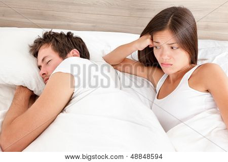 Marriage couple marital problems in bed. Sex problem or other. Woman looking unhappy at man sleeping with back turned. Young multiracial couple, Asian woman and Caucasian man at home in bedroom.