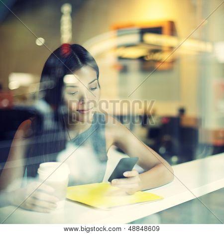 Mujer de estilo de vida Cafe ciudad teléfono bebiendo un mensaje de texto de mensajes de texto de café en aplicación para smartphone sentado