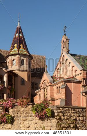 Fortified walls and church of Eguisheim village along the famous wine route in Alsace, France