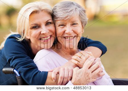 cheerful middle aged woman embracing disabled senior mother outdoors