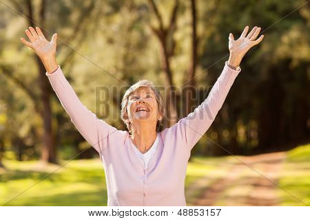 healthy elderly woman looking up with arms outstretched outdoors
