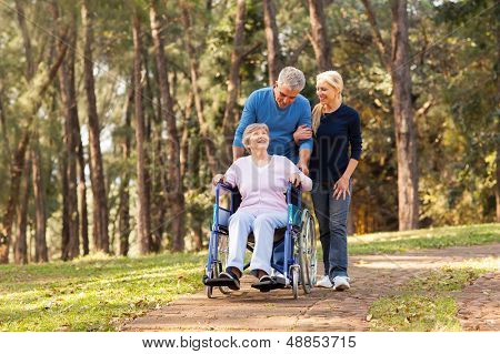 caring couple taking their disable senior mother for a walk at the park