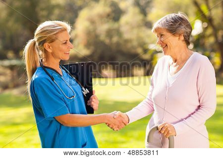 beautiful mid aged nurse handshaking senior patient outdoors