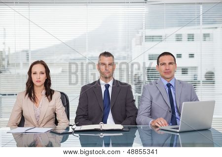 Serious business people waiting for interview in bright office