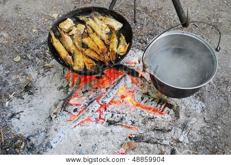 The Stake Is Fried Fish In A Frying Pan And Some Heated Pot