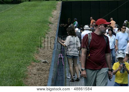 WASHINGTON, DC - JULY 29: A tourist touches the Vietnam Memorial on July 29, 2013 in Washington. The memorial honors U.S. service members who fought in the Vietnam War.