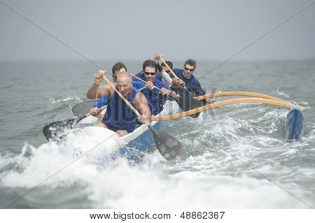 Crew of a racing outrigger canoe on water