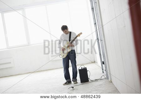 Full length of young man playing electric guitar in empty warehouse