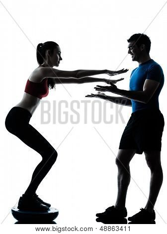 personal trainer man coach and woman exercising squats on bosu silhouette  studio isolated on white background