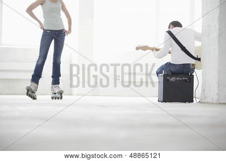 Young man playing electric guitar with woman wearing inline skate in empty warehouse