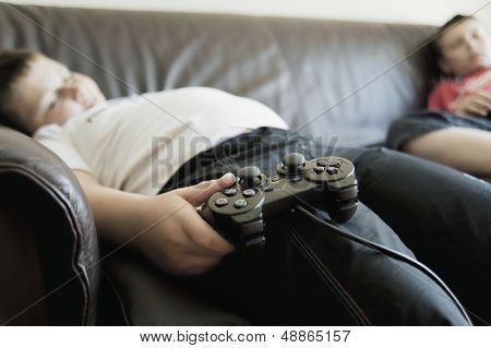 Two boys sleeping on sofa while holding games consoles