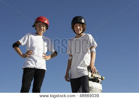 Low angle view of confident teenage skateboarders standing against blue sky