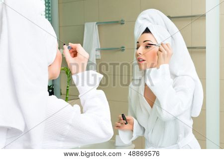 Young woman in the hotel bathroom, suite, refreshing herself and apply makeup