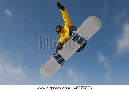 Low angle view of male snowboarder in winter clothes jumping against sky