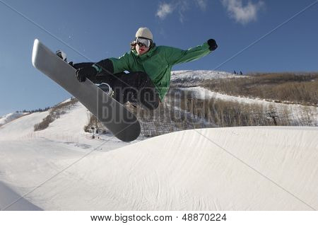 Full length of young snowboarder performing stunts on snowy hill