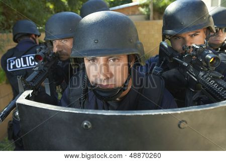 Multi ethnic policemen aiming guns while standing behind shield