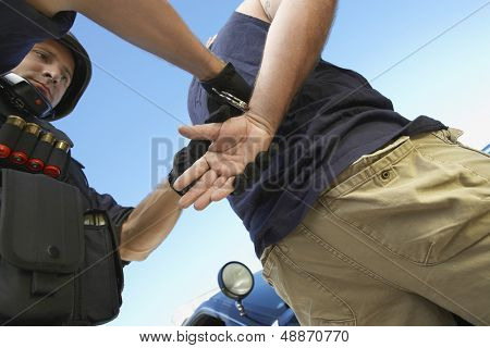 Low angle view of policeman arresting criminal against sky