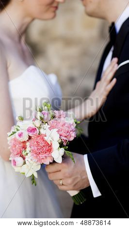 Beautiful white and pink wedding bouquet with bride and groom in the background