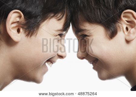 Side view closeup of happy preadolescent siblings with head to head isolated over white background