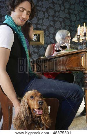 Perro de caricias joven feliz en cena