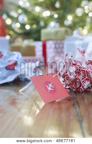 Unwrapped gift paper and tag on hardwood floor with Christmas tree in background