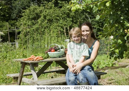 Portrait of happy mother and son with vegetables sitting on picnic table in allotment