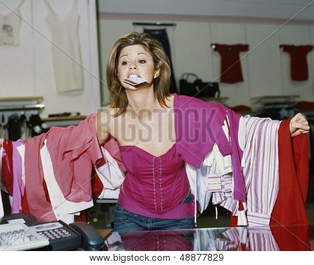 Young shopaholic woman loaded with clothes holding credit card in mouth at store