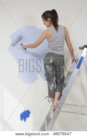 Rear view of young woman painting wall with paintroller while standing on stepladder at home