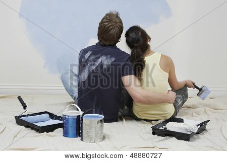 Rear view of young couple looking at paint on wall in unrenovated house