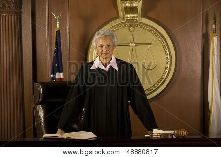 Portrait of confident senior female judge standing in court room