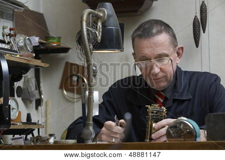 Middle aged repairman working on an old clock in workshop