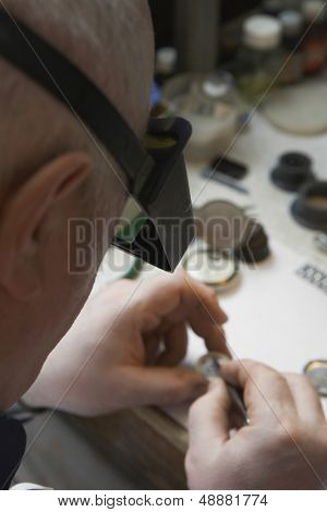Senior repairman working on watch in workshop