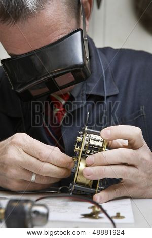 Closeup of middle aged repairman working on an old clock in workshop