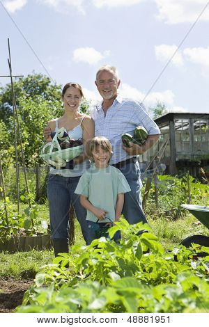 Portrait of happy boy with mother and grandfather holding vegetables in community garden