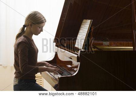 Vista lateral de una niña adolescente tocando el piano