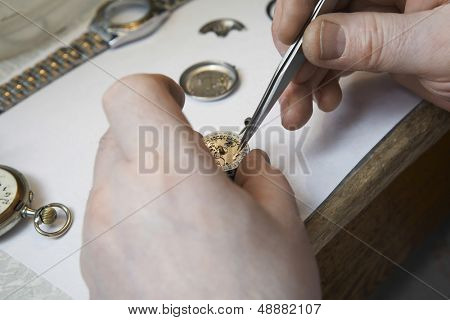 Closeup of repairman's hands working on watch in workshop