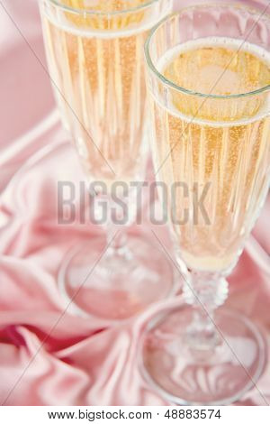 Sparkling Wine On Pink Satin Background