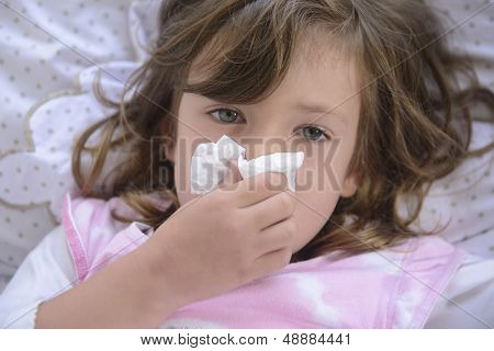 Sick little girl sneezing in bed